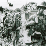 A rifle squad of the 173rd Airborne on a search and destroy mission in Phuoc Tuy province (III Corps), late in 1966.  The two soldiers behind the lead man carry mortar base-plates.